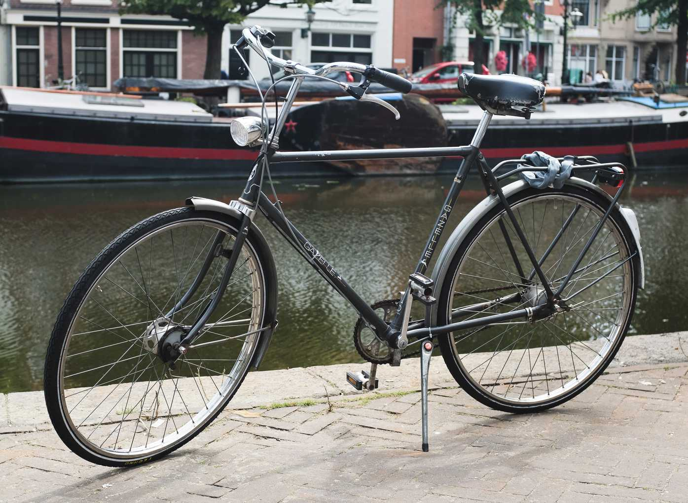 Gray bicycle alongside a canal