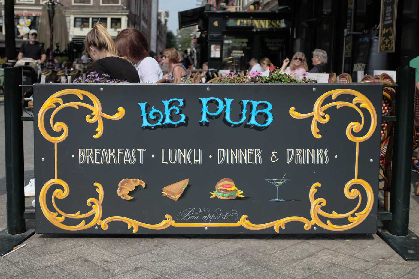 A handpainted sign for a pub with outdoor seating