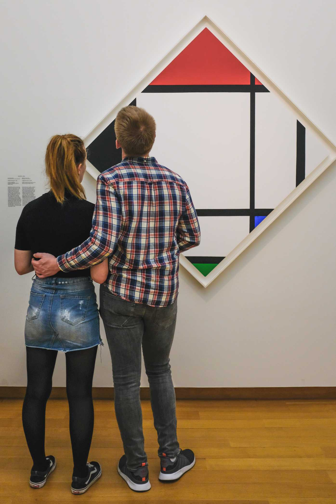 A young couple looks at painting from the art movement De Stijl