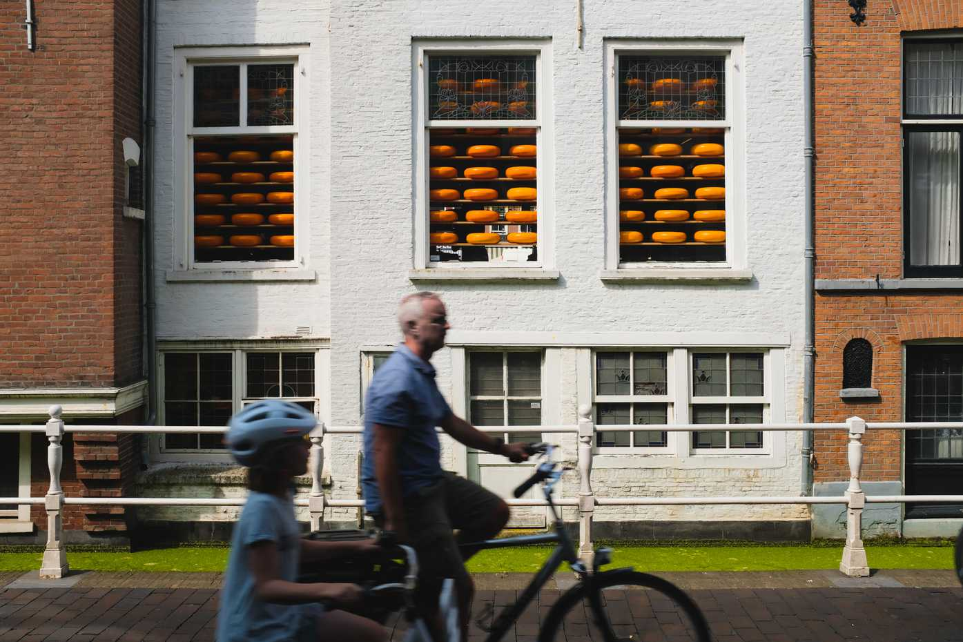 A father and daughter bike past a cheese shop